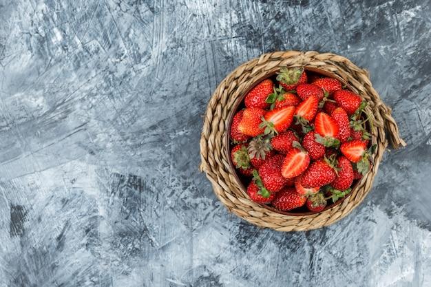 어두운 파란색 대리석 배경에 고리 버들 플레이스 매트에 딸기의 그릇. 평면도. 텍스트를위한 여유 공간