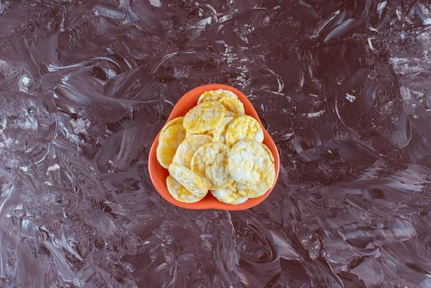 大理石のテーブルの上に、おいしいチーズチップスのボウル。