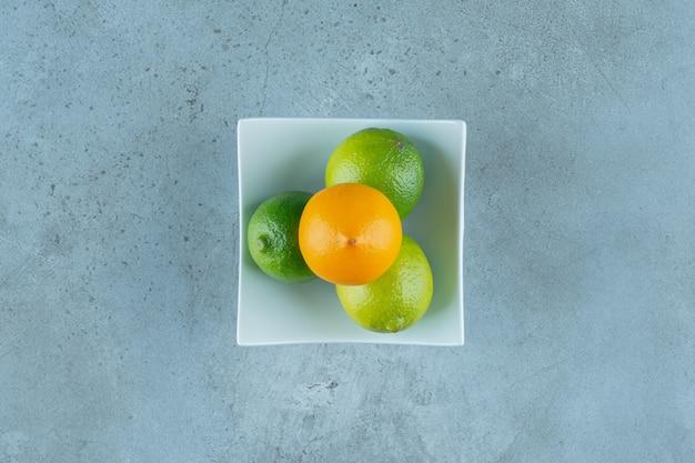 Чаша вкусных лимонов на мраморном фоне. фото высокого качества