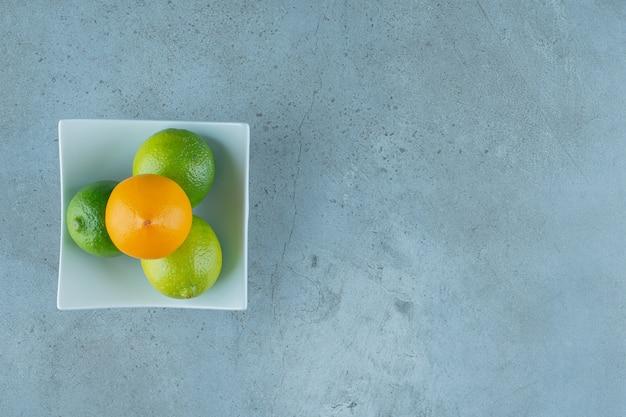 大理石の背景に、おいしいレモンのボウル。高品質の写真