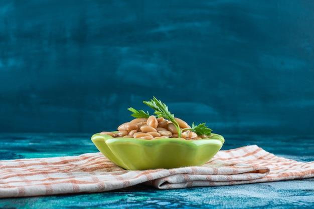 青いテーブルの上に、ティータオルの上に歯ごたえのあるベイクドビーンズのボウル。