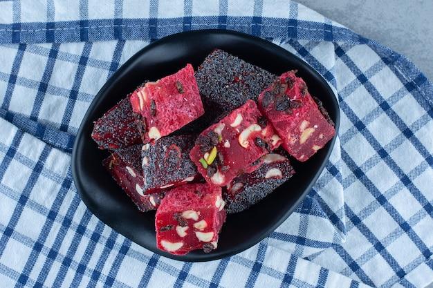 ティータオルの上、大理石のテーブルの上に、トルコ菓子のボウル。