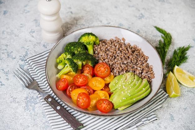 Миска веганской еды, веганский ужин из вареной гречки, цветных помидоров, авокадо и брокколи. вид сверху, выборочный фокус