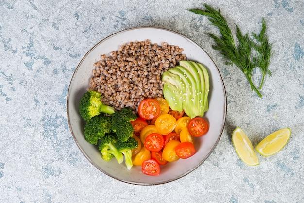 Миска веганской еды, веганский ужин из вареной гречки, цветных помидоров, авокадо и брокколи. вид сверху