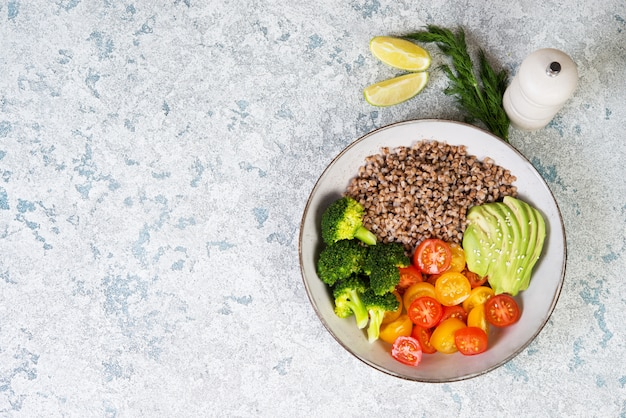 Миска веганской еды, веганский ужин из вареной гречки, цветных помидоров, авокадо и брокколи.