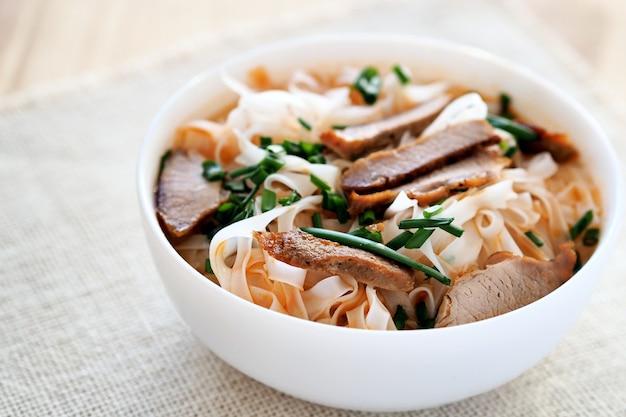 Чаша вьетнамской рисовой лапши с жареным мясом, зеленью и острым бульоном.