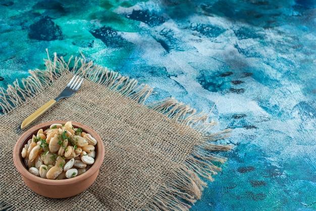 青いテーブルの上のテクスチャのフォークの横にある白豆のボウル。
