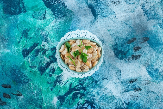 파란색 배경에 파 슬 리와 흰 콩의 그릇.