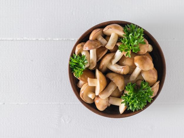 야생 버섯과 파슬리의 그릇은 흰색 나무 테이블에 나뭇잎. 상단에서보기. 천연 채식 요리.