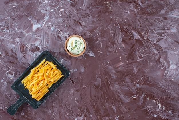 大理石のテーブルの上に、ボードにヨーグルトとポテトのフライドポテトを入れたボウル。