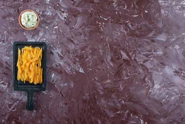 대리석 테이블에 보드에 요구르트와 감자 튀김 한 그릇.