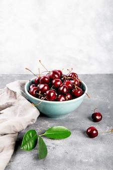 테이블에 밝은 회색 배경 여름 딸기에 그릇 익은 체리