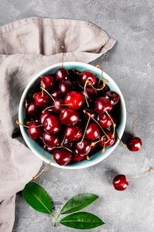 밝은 회색 배경 위에 있는 잘 익은 체리 한 그릇은 탁자 위에 있는 여름 열매를 볼 수 있습니다.