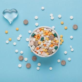 파란색 배경에 많은 약과 유리 심장이 있는 그릇. 플랫 레이.
