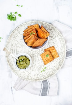 흰색 바탕에 집에서 만든 바삭한 치즈 크래커가 있는 그릇