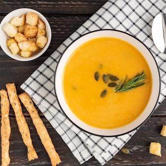 Grossini 빵 막대기와 어두운 나무 배경에 resemary 호박 크림 수프와 그릇. 평면도.