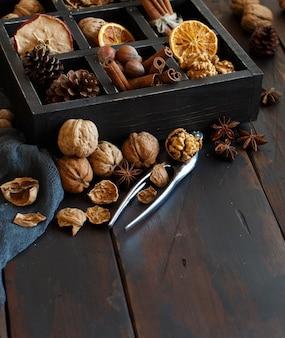 木製のテーブルの上のスパイスとナッツでいっぱいの箱がクローズアップ