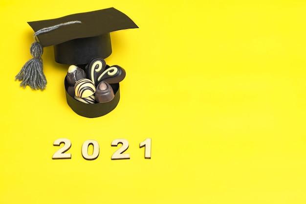 대학원 모자 형태의 초콜릿 상자. 초콜릿 하루 개념입니다. 컬러 배경에 졸업 2021입니다.