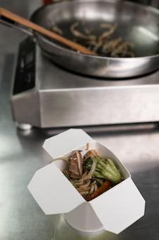 Коробка с азиатскими блюдами на вынос на металлической поверхности. быстрая и удобная доставка из ресторана