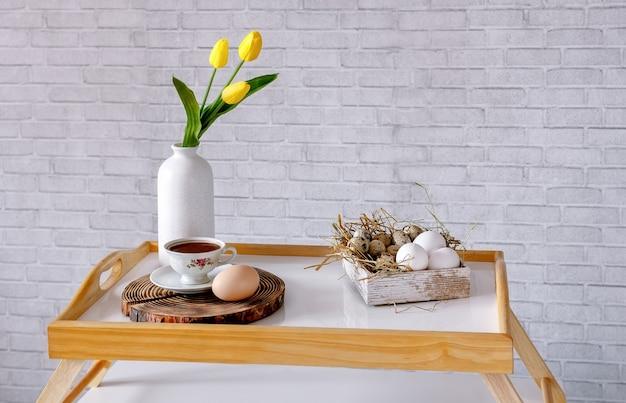 로프트 스타일의 벽에 기대어 커피 테이블에 계란, 차 한 잔, 노란 튤립 꽃병이 든 상자. 좋은 아침. 집에서 편안함을 느끼는 개념.