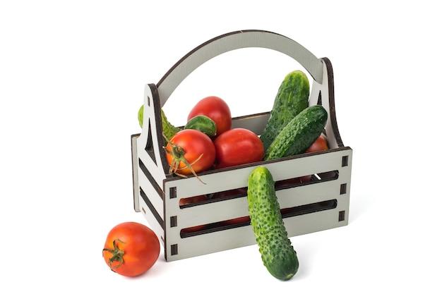 흰색 배경에 격리된 신선한 오이와 토마토가 있는 상자. 야채의 신선한 작물입니다. 프리미엄 사진
