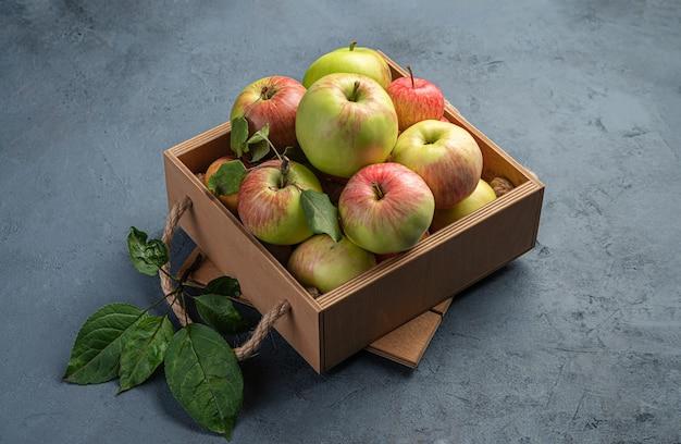 濃いグレーブルーの背景に天然の農場のリンゴが入った箱