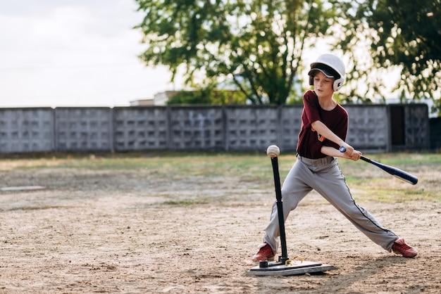 Мальчик, бейсболист, бьет по мячу бейсбольной битой