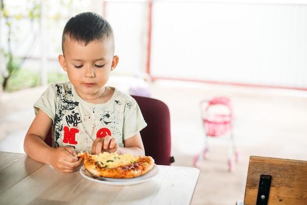 Мальчик, ребенок на улице ест мини пиццу очень аппетитно
