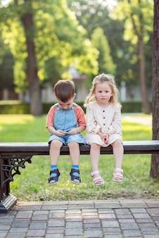 男の子と女の子が公園のベンチに座っている女の子が頬に男の子にキスします