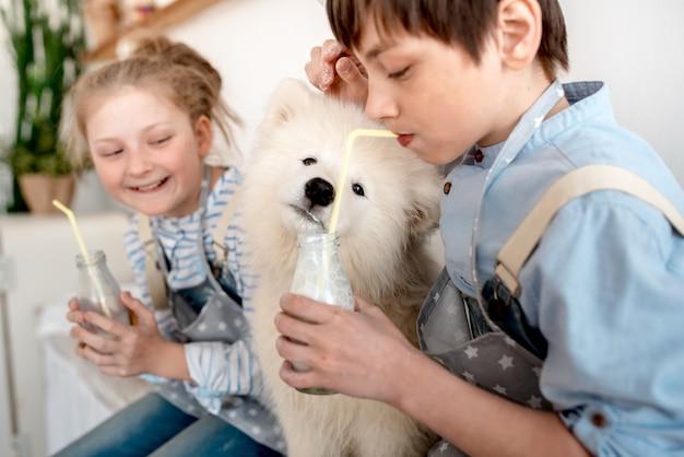 Мальчик и девочка пьют молоко через трубочку, а щенок слизывает капли из бутылки