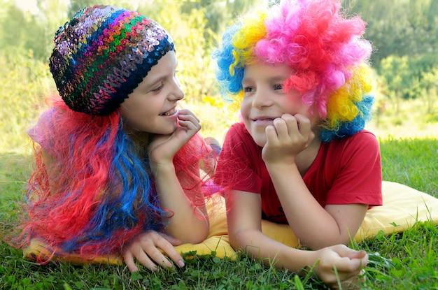 Мальчик и девочка в забавных париках вместе отдыхают на природе.
