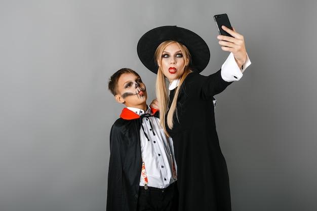 Мальчик и девочка в костюмах хэллоуина делают селфи на сером фоне стены. фото высокого качества