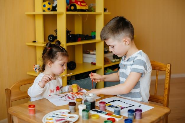 소년과 소녀가 함께 놀고 페인트 칠합니다. 레크리에이션과 오락. 집에있어