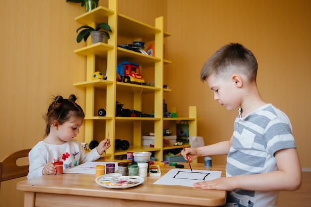 Мальчик и девочка играют вместе и рисуют. отдых и развлечения. оставайся дома.