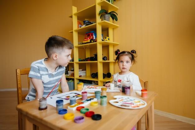 Мальчик и девочка вместе играют и рисуют. отдых и развлечения. оставайся дома.