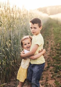 소년과 소녀 형제와 자매는 여름에 들판에서 놀고 있습니다. 행복한 여름방학. 시골길에 소년과 소녀입니다. 밀밭