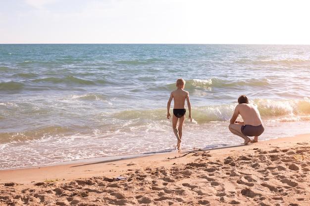 Мальчик и его отец гуляют по песчаному берегу моря, освещенному ярким солнечным светом летом.