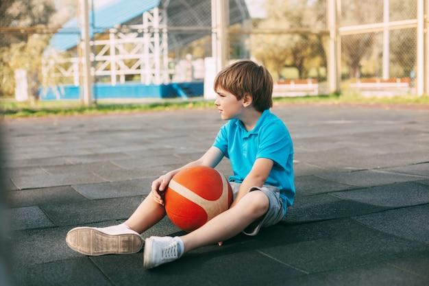 青いtシャツを着た男の子のバスケットボール選手がボールを持ってバスケットボールコートに座っています