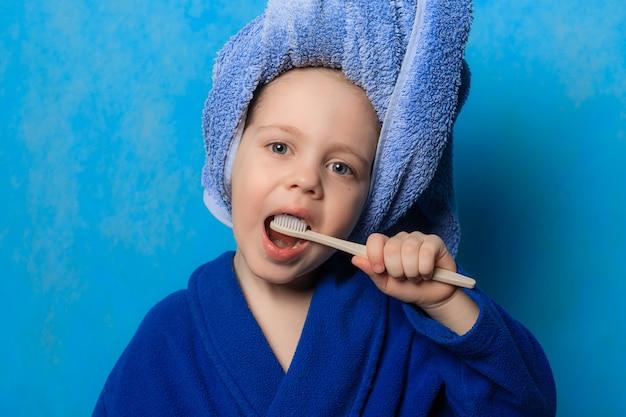 소년은 파란색 배경에 그의 머리 주위에 가운과 수건으로 양치질
