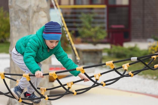 男の子が遊び場でロープのはしごを登る