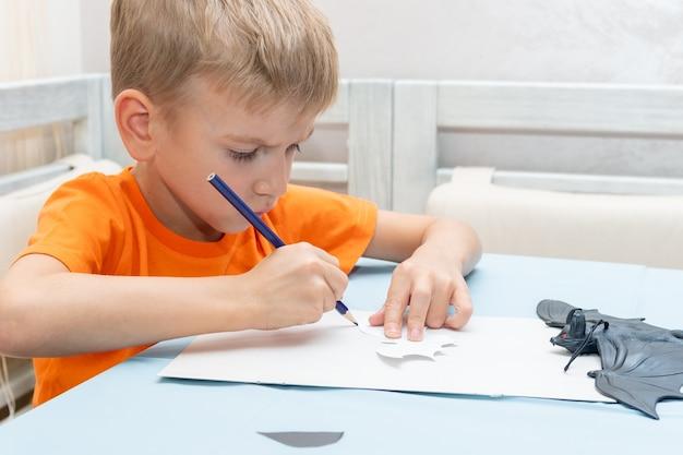 Мальчик рисует и вырезает дома украшение на хэллоуин из черной бумаги. поделки своими руками. ребенок лепит из бумаги черных летучих мышей, оригами