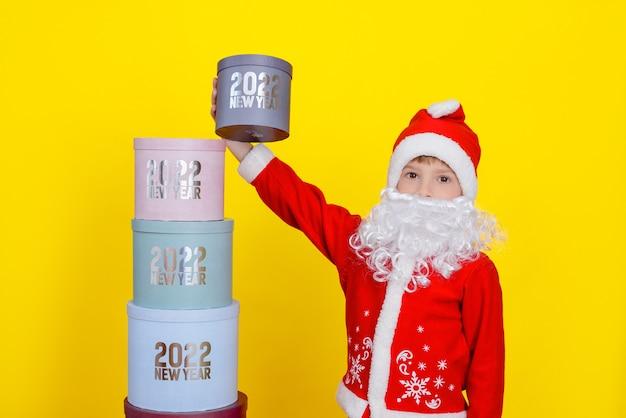 Sanat claus의 옷을 입은 소년이 2022년 새해와 함께 맨 위의 선물 상자를 집어 들었습니다.