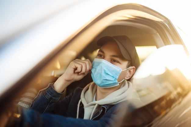Мальчик водит машину, примеряет и поправляет медицинскую стерильную маску во время карантина по пандемии коронавируса