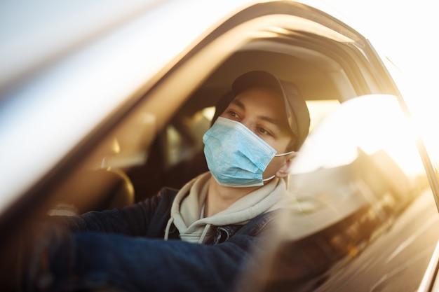 Мальчик водит машину в медицинской стерильной маске во время карантина по пандемии коронавируса