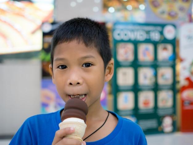 Мальчик ест мороженое в торговом центре с размытым фоном