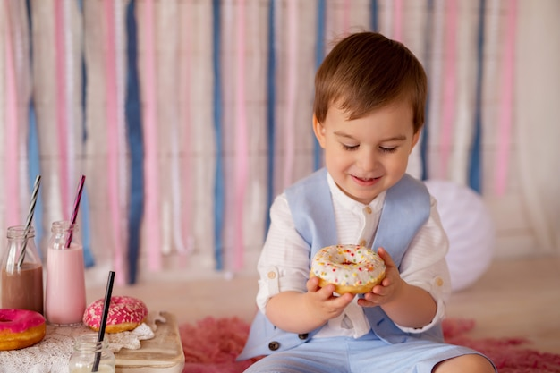 男の子はドーナツを食べ、ストローから牛乳を飲みます。子供のための素晴らしい食べ物。