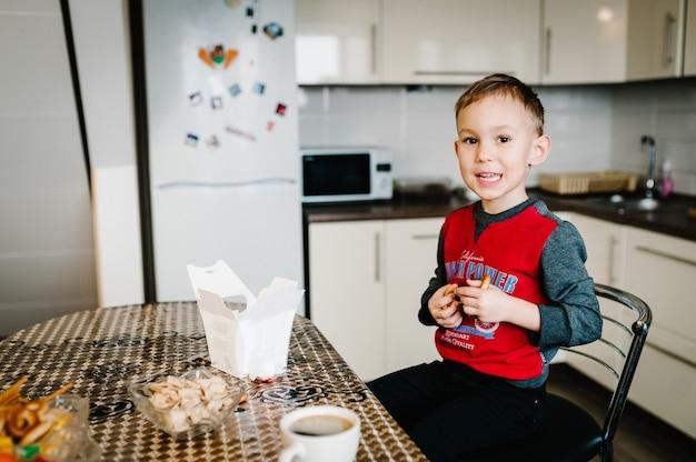 Мальчик ест вкусный свежеиспеченный бублик. сын пьет чай утром, завтракает на кухне дома. семья, еда и люди концепции.
