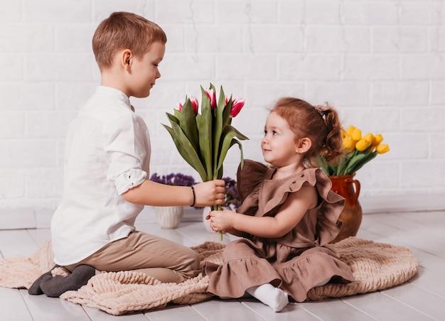 Мальчик дарит девочке букет тюльпанов. цветы к празднику