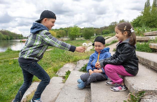 Мальчик дарит маленькой девочке одуванчик на природе.