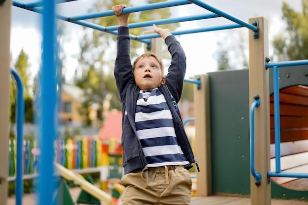 猿の棒にぶら下がっている少年彼の兄弟は彼の頭の上からのぞきます遊び場での運動